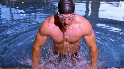 Muscular swimmer emerging from pool and pulling himself up