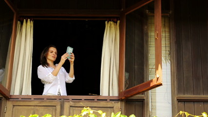 Woman taking photo with cellphone from window in country house