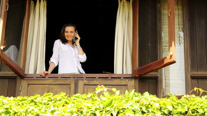 Woman talking on cellphone in country house window