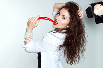 young beautiful woman with red lips biting a chili pepper