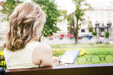 Young woman sitting on bench in park using tablet.