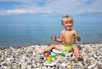 Kid soiled by paints on beach