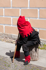 executioner sitting near the wall on the street
