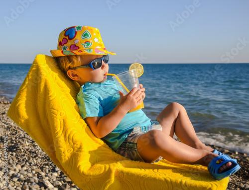 Leinwanddruck Bild Boy kid in armchair with juice glass on beach