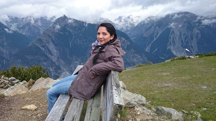 Junge Frau auf Bank in bergpanorama