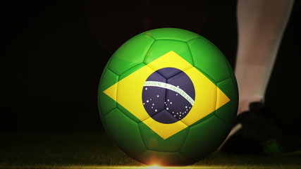 Football player kicking brazil flag ball