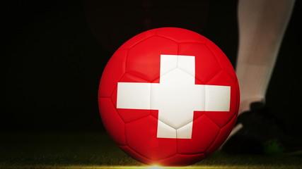 Football player kicking swiss flag ball