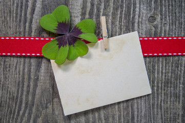 Kleeblatt mit Karte, rotem Band auf Holzhintergrund