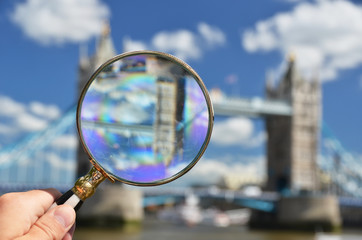 Magnifying glass in the hand against Tower bridge in London