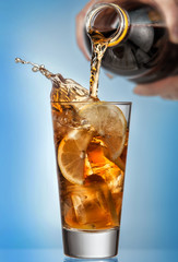 Glass of splashing iced tea with lemon on blue background