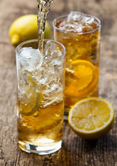 Pouring iced tea with lemon