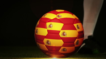 Football player kicking spain flag ball