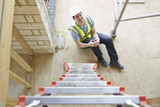 Construction Worker Falling Off Ladder And Injuring Leg - 67553194