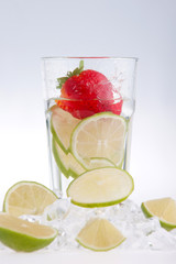 Glass Of Drink With Ice Cubes And Fruits On White