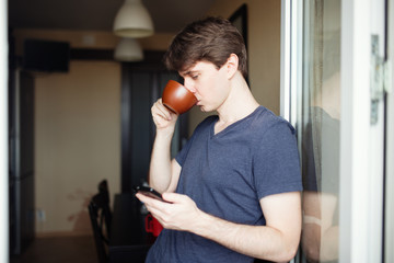 Man drinking coffee and using mobile smartphone