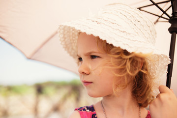 Little cute girl holding an umbrella, close up portrait