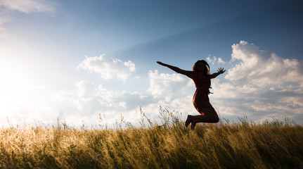 Happy woman jumping in the meadow at the sunset
