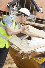 Builder Putting Waste Into Rubbish Skip