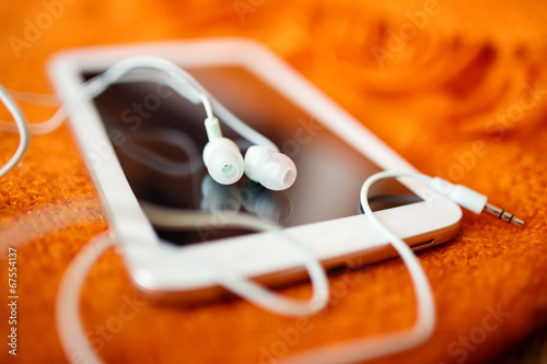 Leinwanddruck Bild White earphones and tablet pc, close up photo, small dof