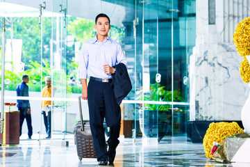 Asian Man walking in hotel lobby with trolley