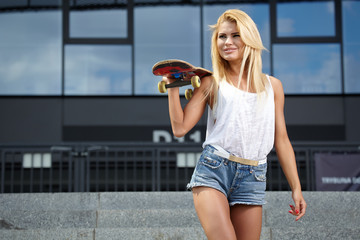 Beautiful young woman with skateboard in city