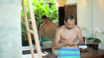 Man in bath towel texting on smartphone in the bathroom