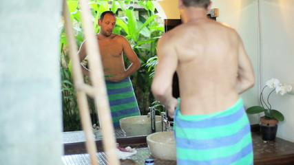 Man in bath towel in front of the mirror after shower