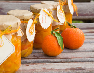 Homemade tangerine marmalade in the glass on the wooden surface