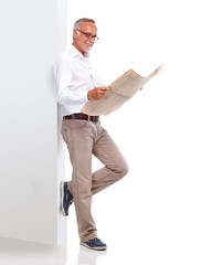 Mature man leaning against a wall and reading newspaper