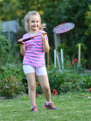 happy little girl playing badminton
