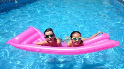 Niños en la piscina sobre colchoneta
