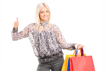Fashionable woman holding shopping bags and giving thumb up