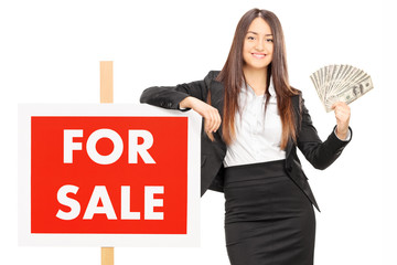 Female real estate agent holding money by a for sale sign