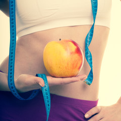 Diet healthy nutrition. Fit girl with measure tape, fruit apple.