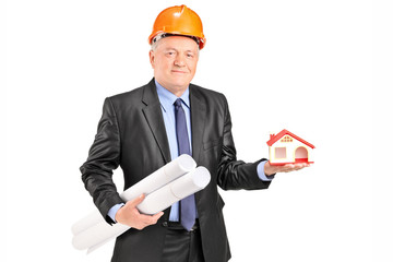 Mature architect holding plans and a model house