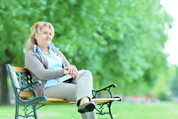 Mature pensive woman sitting alone in the park