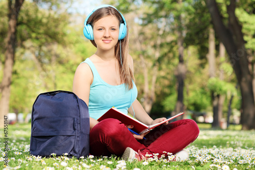 Female student reading a book in park
