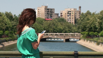 Girl standing on a bridge and texting