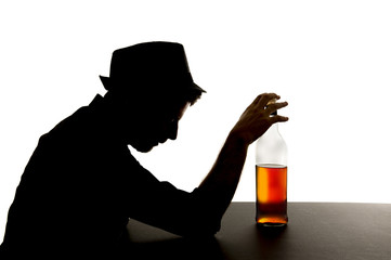silhouette of alcoholic drunk man drinking whiskey bottle