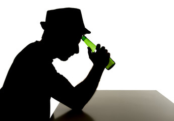 silhouette of alcoholic drunk man drinking beer bottle in abuse