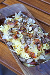 Pasta with bacon and truffles on a wooden plate