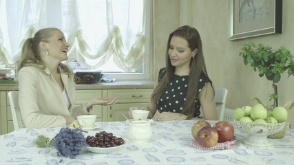 Two attractive happy women having fun at dining table