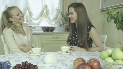 Two attractive smiling women having tea at dining table