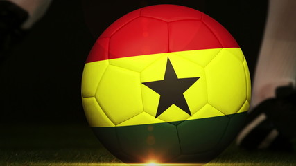 Football player kicking ghana flag ball