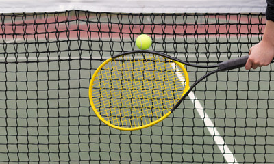 Player hits tennis ball into net