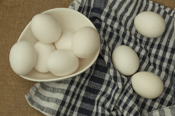Eggs in a white bowl with napkin on table mat.
