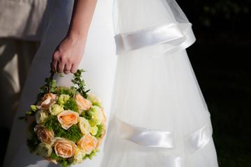 La sposa cammina con il proprio boquet in mano