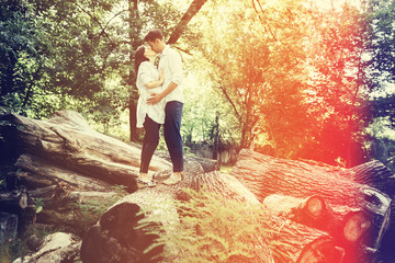Happy and young pregnant couple hugging in nature. Vintage retro