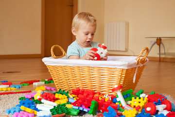 Baby girl  with toys in basket