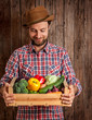 Happy farmer holding wooden box of vegetables